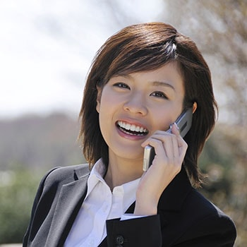 A woman holding a cell phone and smiling to illustrate our dental services in Sammamish WA includes cosmetic dentistry