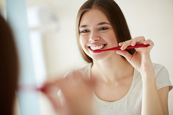 A young woman brushing her teeth and smiling to show proper preventative care is important