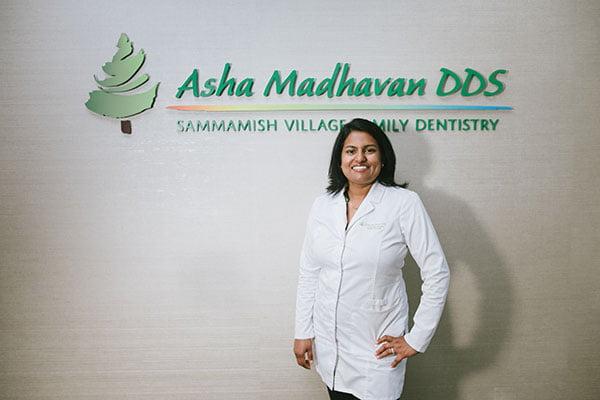Dr. Madhavan standing in front of her logo